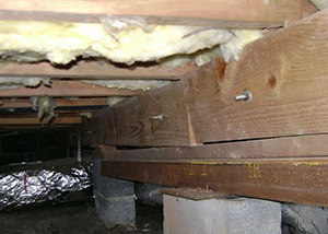 sagging crawl space with wooden shimming a Brazeau crawl space