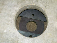 A three piece foundation slab bracket assembled underneath a concrete slab floor.