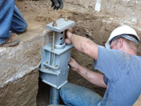 Foundation repair contractors installing the foundation bracket in Medicine Hat.