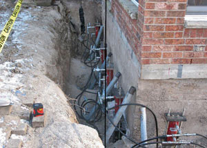 Foundation push piers installed around a house with a foundation settlement issues in Dunmore