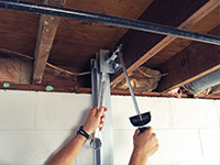 Straightening a foundation wall with the PowerBrace™ i-beam system in a High River home.