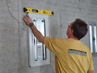 Positioning a wall plate cover on a foundation wall in Cochrane.