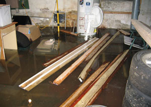 A severely flooding basement in Brooks, with lumber and personal items floating in a foot of water