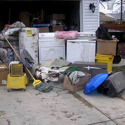 Soaked, wet personal items sitting in a driveway, including a washer and dryer in Cochrane.