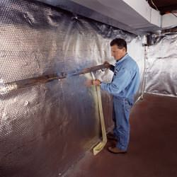 Installation of a radiant heat and vapor barrier on a basement wall in Sunnynook